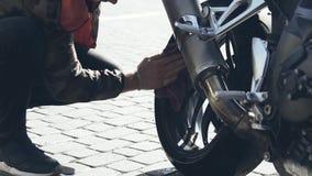 Un uomo lucida un motociclo con un panno su una rondella video d archivio