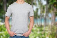 Un uomo in maglietta grigia e denim tiene le sue mani in tasche Fotografia Stock