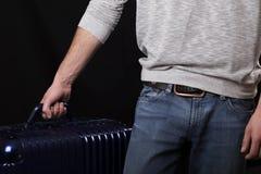 Un uomo in maglione grigio e blue jeans con una valigia blu scuro Immagine Stock Libera da Diritti