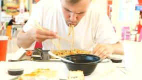 Un uomo mangia l'alimento cinese in un fast food 4K Movimento lento video d archivio
