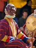 Un uomo mascherato che fa musica durante il tsechus Immagine Stock
