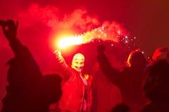 Un uomo mascherato che tiene un chiarore rosso durante le celebrazioni di 2015 nuovi anni al quadrato di Wenceslas, Praga Immagine Stock