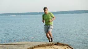 Un uomo maturo è impegnato in ginnastica nel mare all'alba Funziona lungo il litorale in cuffie, movimento lento eccellente video d archivio