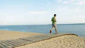 Un uomo maturo è impegnato in ginnastica nel mare all'alba Funziona lungo il litorale in cuffie, movimento lento eccellente archivi video