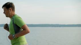 Un uomo maturo è impegnato in ginnastica nel mare all'alba Funziona lungo il litorale in cuffie, movimento lento eccellente stock footage