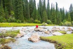 Un uomo medita fra il fiume della montagna Fotografia Stock Libera da Diritti