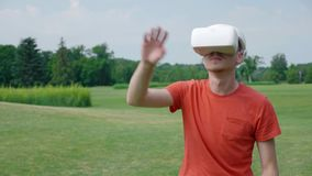 Un uomo mette una cuffia avricolare di VR sulla sua testa e sul gioco del gioco virtuale nel parco