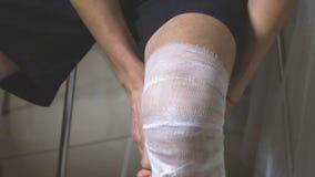 Un uomo mette una fasciatura sulla sua gamba stock footage