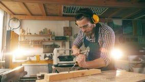 Un uomo modella un pezzo di legno, facendo uso degli strumenti della falegnameria stock footage