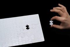 Un uomo monta il pezzo di puzzle su fondo nero immagine stock libera da diritti