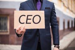 Un uomo mostra una compressa del cartone con il CEO della parola ? fotografia stock