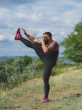 Un uomo muscolare allegro all'aperto Un uomo muscolare sexy su uno sfondo naturale Un culturista che fa gli esercizi di riscaldam Immagini Stock Libere da Diritti