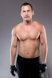 Un uomo muscolare di 30 anni, sui precedenti grigi Immagini Stock Libere da Diritti