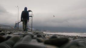 Un uomo negli stivali di trekking va verso la torre Spiaggia vuota di autunno stock footage