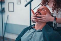 Un uomo in un negozio di barbiere per i capelli e una barba professionali di trattamento immagini stock libere da diritti