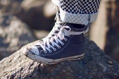 Un uomo nei supporti sporchi blu delle scarpe da tennis su una roccia fotografia stock libera da diritti