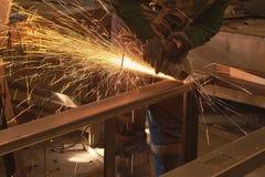 Un uomo nei tagli che di lavoro della forma un metallo ha visto con un bulgaro fotografie stock