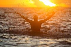Un uomo nel mare tropicale alza lo spruzzo con un'ondata di suo ha immagini stock libere da diritti