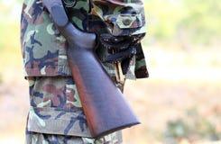Un uomo nel vestito del soldato con il fucile e le pallottole Fotografia Stock Libera da Diritti