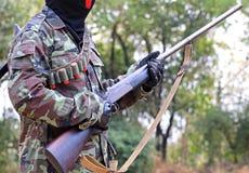 Un uomo nel vestito del soldato con il fucile e le pallottole Fotografia Stock