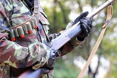 Un uomo nel vestito del soldato con il fucile e le pallottole Immagini Stock
