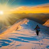 Un uomo nell'inverno di tramonto della montagna Immagini Stock
