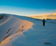 Un uomo nell'inverno di tramonto della montagna unico! Immagini Stock