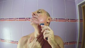 Un uomo nelle rasature del bagno con un rasoio i resti di vegetazione dalle suoi guance e mento archivi video