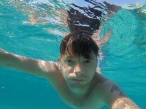 Un uomo nuota nel mare è impegnato nell'immersione subacquea Immagini Stock