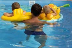 Un uomo nuota in uno stagno con due bambini nei cerchi gonfiabili gialli fotografia stock