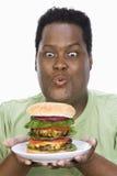 Un uomo obeso che esamina hamburger Fotografia Stock Libera da Diritti