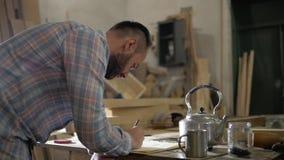 Un uomo in un'officina di carpenteria effettua i calcoli alla tavola stock footage
