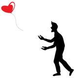 Un uomo in ombra ha lasciato il cuore a forma di pallone rosso volare via Fotografia Stock