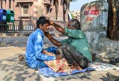 Un uomo ottiene una rasatura ad un negozio di barbiere della via fotografia stock libera da diritti