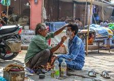 Un uomo ottiene una rasatura ad un negozio di barbiere della via immagini stock libere da diritti