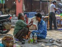 Un uomo ottiene una rasatura ad un negozio di barbiere della via immagine stock libera da diritti