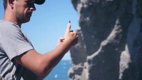 Un uomo piacevole prende le immagini delle rocce ed ondeggia nella macchina fotografica, mani nella vittoria di gesto HD, 1920x10 archivi video