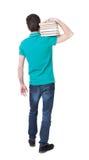 Un uomo porta un mucchio pesante dei libri Vista posteriore Fotografia Stock Libera da Diritti
