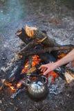 Un uomo prende un bollitore dalla mano con un fuoco immagine stock