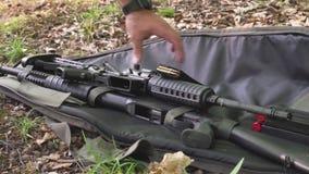 Un uomo prende un fucile di assalto dalla terra e da una rivista/clip con le pallottole Pistole, armi, fucile da caccia e fucile  stock footage