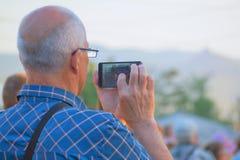 Un uomo prende le immagini su uno smartphone sulla via un giorno di estate Fotografie Stock