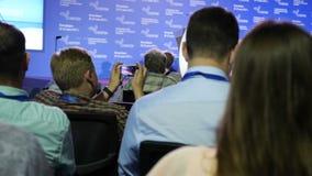 Un uomo prende una foto dal telefono cellulare ad una riunione d'affari, ad un seminario o ad una conferenza l'uomo d'affari pren video d archivio