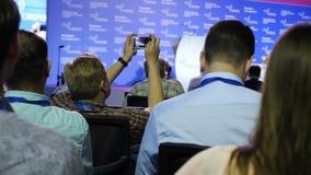 Un uomo prende una foto dal telefono cellulare ad una riunione d'affari, ad un seminario o ad una conferenza l'uomo d'affari pren stock footage