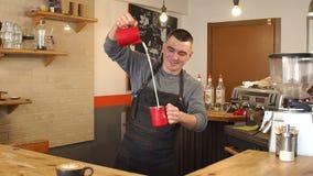 Un uomo prepara il cappuccino in una caffetteria moderna Un uomo versa il latte in caffè stock footage