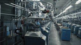 Un uomo prepara un posto di lavoro alla fabbrica dell'indumento video d archivio