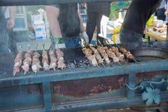 Un uomo prepara sul barbecue delizioso della griglia Kebab sugli spiedi Fotografie Stock Libere da Diritti