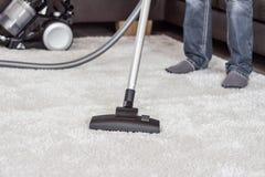 Un uomo pulisce il tappeto con un aspirapolvere Immagini Stock Libere da Diritti