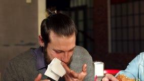 Un uomo pulisce la sua bocca con un tovagliolo durante il pranzo ad un ristorante stock footage