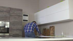 Un uomo pulisce, lava l'agente di sgrassatura moderno della cucina, lento-Mo, housecleaning stock footage