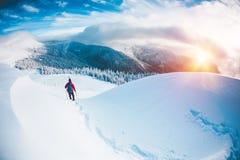 Un uomo in racchette da neve nelle montagne nell'inverno Immagini Stock